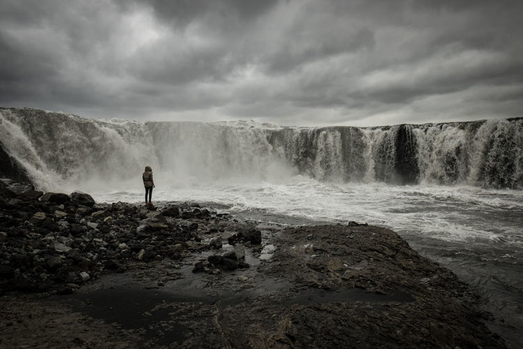 Rear view of man standing by waterfall against sky