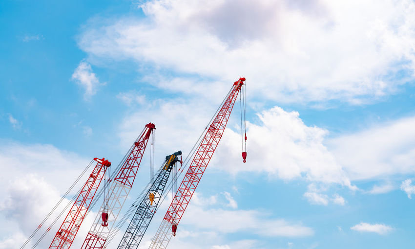 Crawler crane against blue sky and white clouds. real estate industry. red crawler crane.