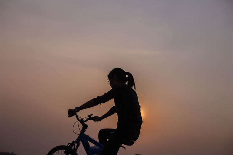 Silhouette woman riding bicycle against sky during sunset