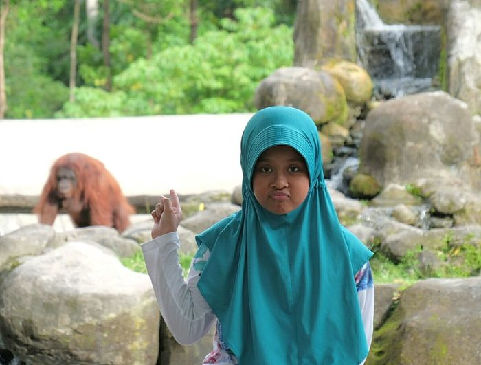 Portrait of girl wearing hijab pointing at orangutan at zoo