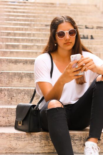 #fashion #photography #lisbon Holding One Person Young Adult Lifestyles Young Women Women The Fashion Photographer - 2018 EyeEm Awards Real People Glasses Adult Sunglasses Casual Clothing Fashion Smart Phone Leisure Activity Sitting Front View Day Architecture
