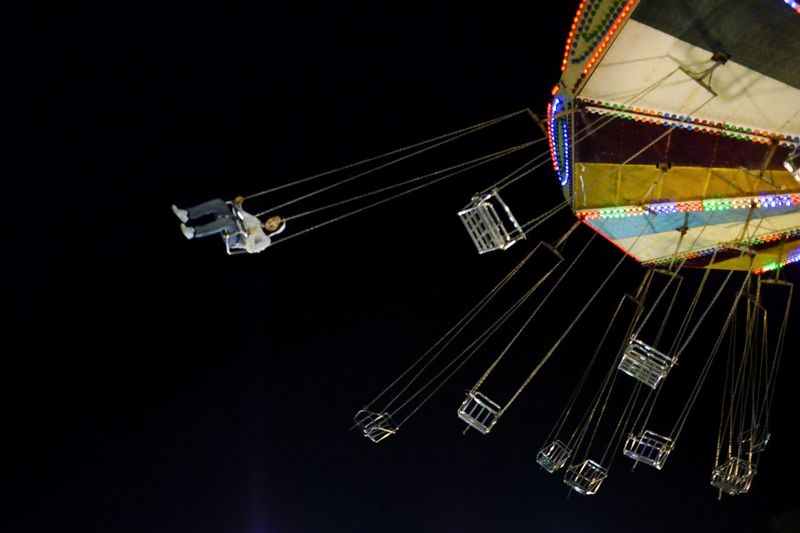 Low angle view of ferris wheel against black background