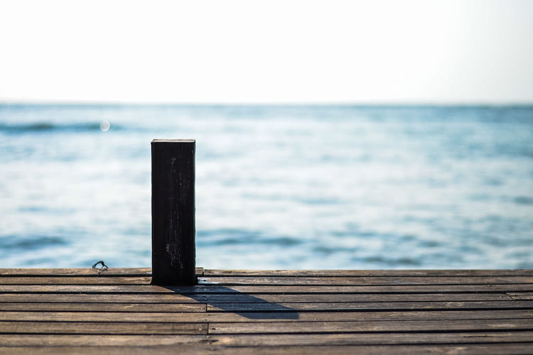 Close-up of wooden pier over sea against clear sky