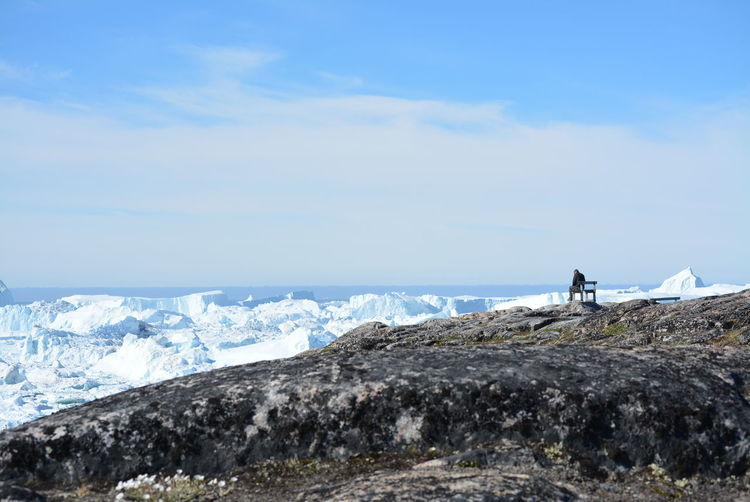 Rear View Of Man Sitting On Rock Formation By Glacier Against Sky