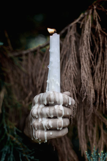 Close-up of a hand holding lit candle