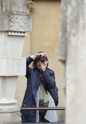 Woman Photographing Through Camera While Standing Against Wall