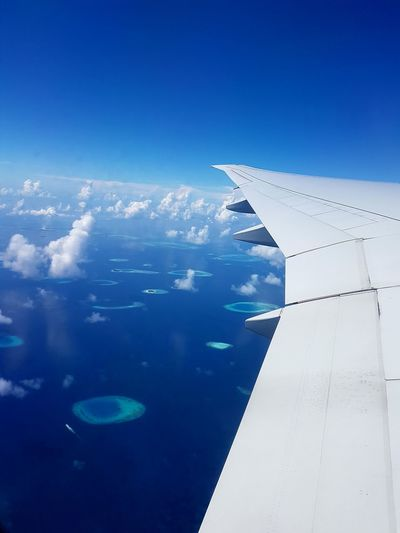Aerial view of airplane wing over sea against blue sky