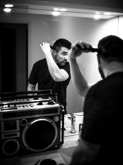 Man cutting hair while looking in mirror