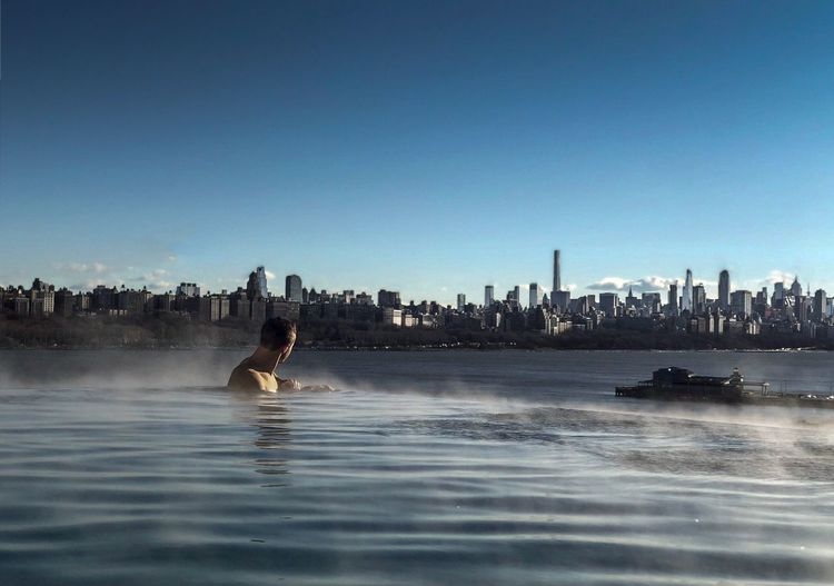 Hot infinity pool Water Architecture Skyscraper Built Structure Waterfront Building Exterior City Urban Skyline Real People Leisure Activity Blue Travel Destinations One Person Clear Sky Men Swimming Day Lifestyles Manhattan View