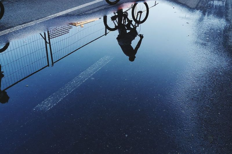 Reflection of man on puddle