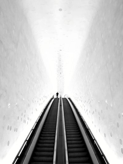 Low angle view of illuminated escalator in tunnel