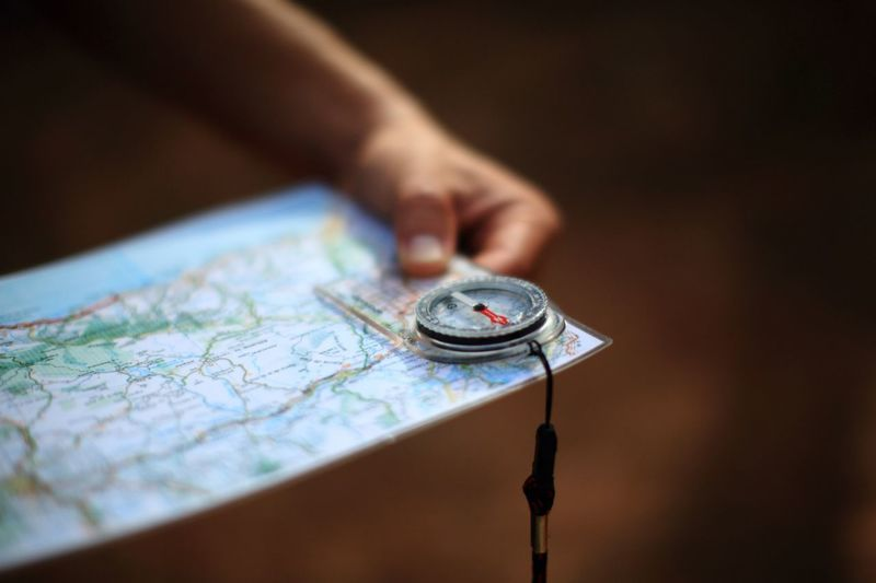 Hand holding map and compass