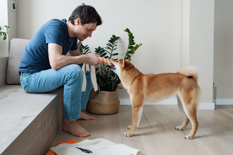 Funny adult man playing with a homemade dog toy with his favorite furry dog friend