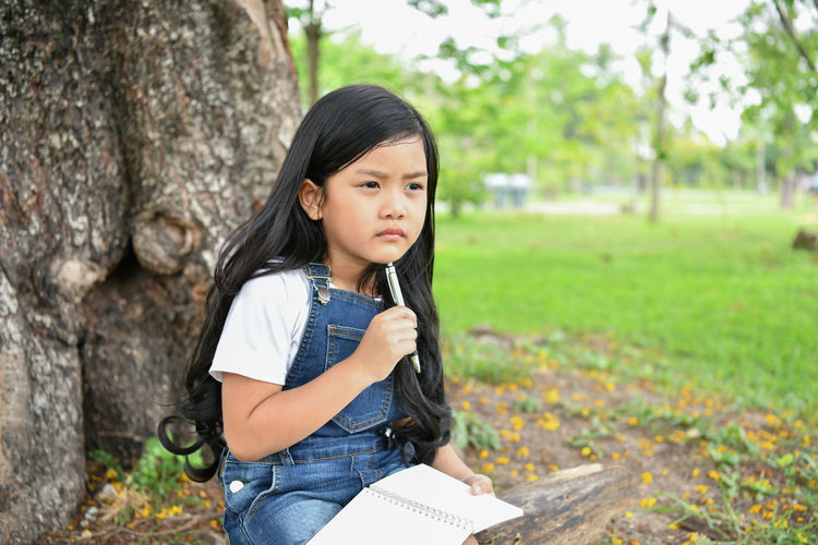 Thoughtful Girl Studying With Sitting Against Tree At Park