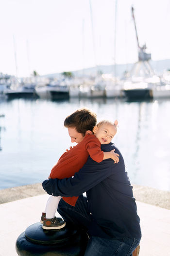 Rear view of father with son on shore