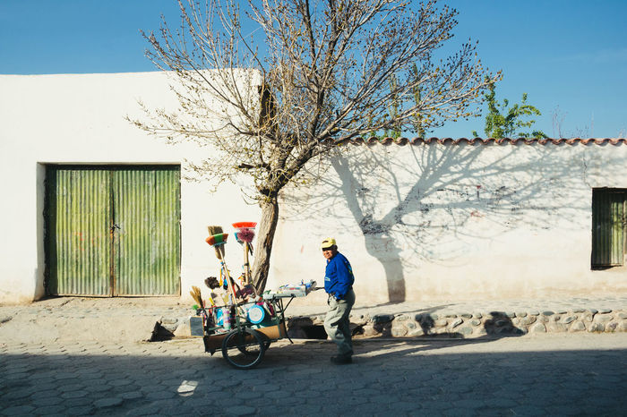 Argentina Building Exterior Day Full Length Land Vehicle Latin America Northern Argentina One Person Outdoors Real People Street Vendor Streetphotography Traditional Tree White Wall The Street Photographer