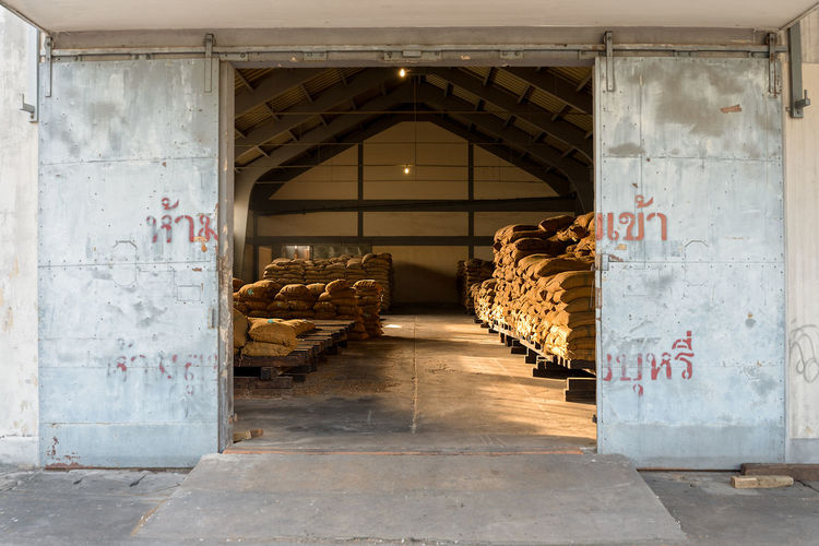 Piled up full hessian sacks awaiting collection in a a large warehouse through an open door. Piles Roof Architecture Built Structure Day Door Way Dry Store Hessian Hessian Bag Hessian Sack High Roof Indoors  No People Open Door Pallets Piled Up Sacks Stacked Storage Text Warehouse