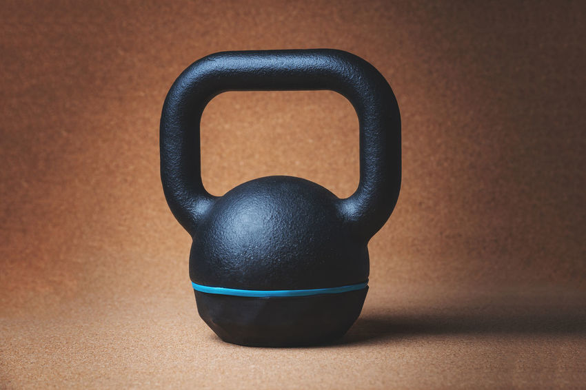 Close up view of a kettlebell - studio shot Cross Black Color Blue Brown Close-up Colored Background Equipment Fit Fitness Focus On Foreground Gym High Angle View Indoors  Kettlebell  Metal No People Shadow Simplicity Single Object Sport Still Life Strength Studio Shot Table Wood - Material
