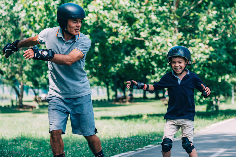 Roller Skating Race, Grandfather and Grandson Having Fun Rollerskating Grandfather Grandson Roller Sport Outdoor Kid Fun Child Instructor Active Ride Rollerblading Learning Teaching Roller Skating Senior Skate Young Happy Blade Rollerblade Road Boy Summer Skater Park Activity Smile Helmet Blades Rollerblader Family Protector Pads Knee Pads Recreation  Protection Safe Sporty Enjoy Rollerblades Balance Old Man People Roller Skate Motion Speed Positive Emotion Cheerful Quality Time