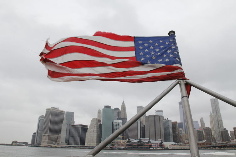 Low angle view of united states flag against buildings in city