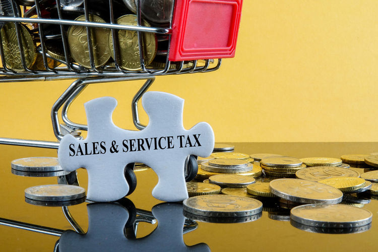 SALES & SERVICE TAX conceptual text. Trolley,coins and jigsaw puzzle with reflection on a yellow background. Sales and shopping concept Shopping Cart Taking Photos Close-up Communication Indoors  Metal No People Sales And Service Tax Sst Still Life Text Western Script Yellow