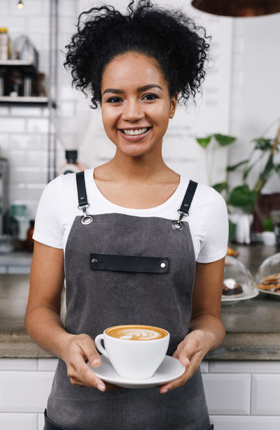 Coffee Coffee Shop Waitress Woman Cafe Cafeteria Cheerful Confidence  Cup Food And Drink Front View Holding Indoors  Looking At Camera Occupation One Person Owner Portrait Real People Restaurant Small Business Smiling Standing Business Stories