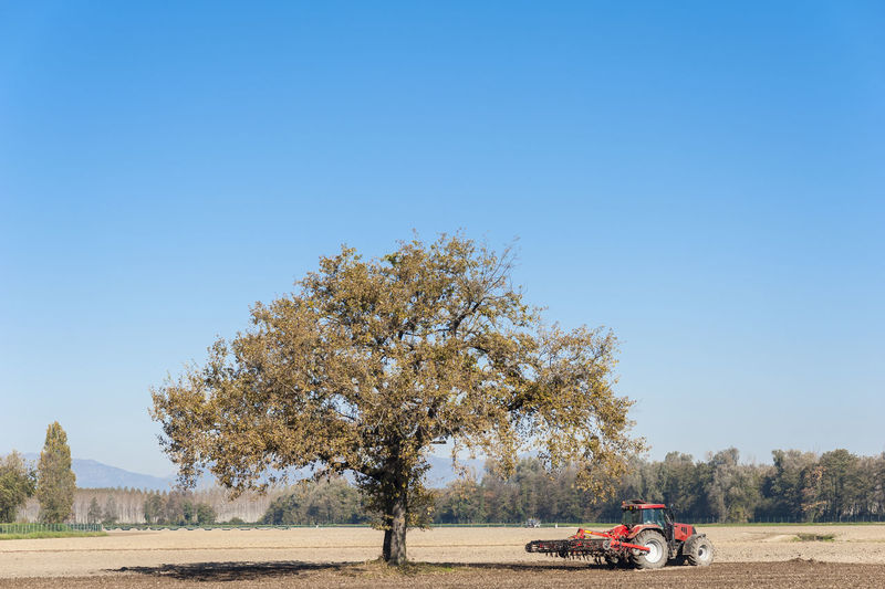 Tractor On Agricultural Field Against Clear Blue Sky