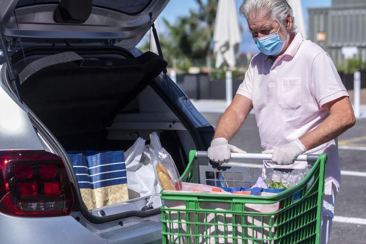 Senior man wearing mask putting groceries in car trunk outdoors