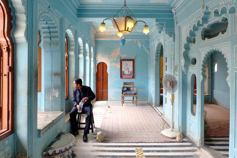 Full Length Of Man Sitting On Chair In Corridor