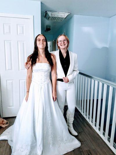 Portrait of bride with female friend at bridal shop