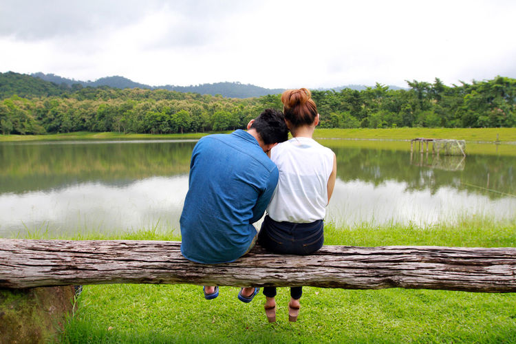 Rear view of couple sitting on lake against sky