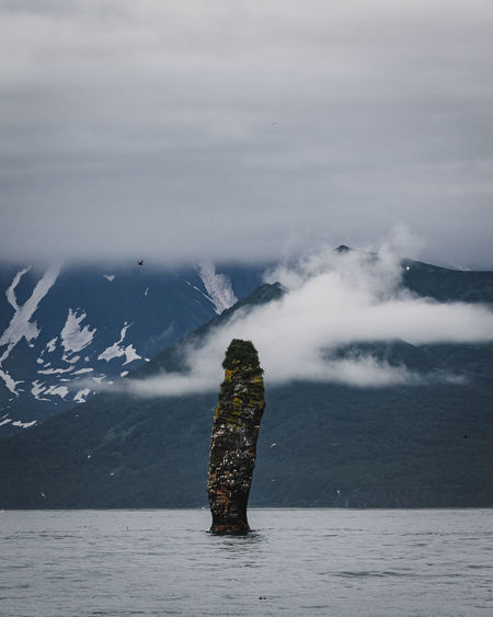 Stack rock in sea with mountains in background