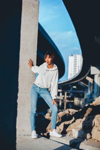 Young woman standing under bridge