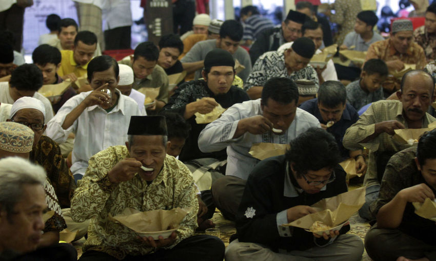 Ramadan in Indonesia. Crowd Large Group Of People Group Of People Men Sitting Real People Adult Women Lifestyles Technology Leisure Activity Communication Activity Architecture Front View Outdoors Young Adult Togetherness Day Teenager