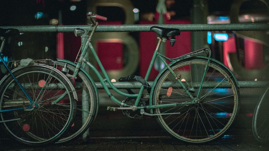 Bicycle parked on railing at night