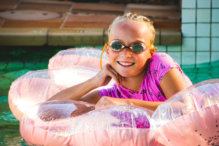 portrait of a young girl relaxing in the pool on pink inflatable Happiness Smiling Portrait Headshot Child One Person Front View Childhood Looking At Camera Cheerful Enjoyment Emotion Lifestyles Leisure Activity Girls Real People Water Innocence Swimming Pool Outdoors Inflatable  Positive Emotion Summertime Vacations Swimming Goggles