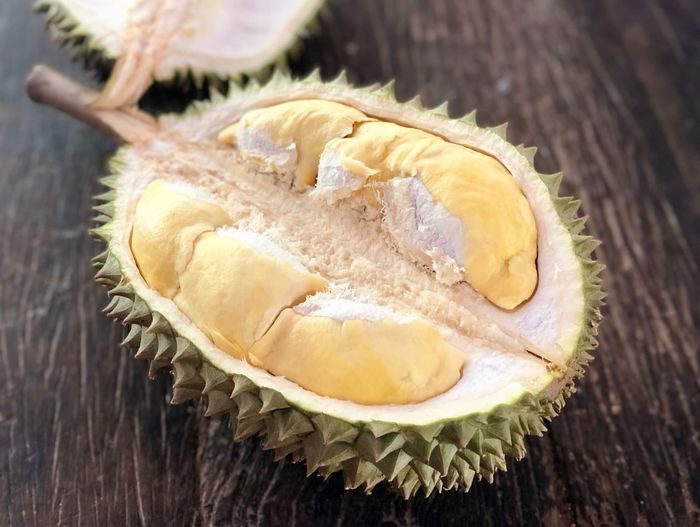 Durian ready to eat on wooden table Food And Drink Food Healthy Eating Wellbeing Close-up Freshness Table Wood - Material High Angle View Cross Section Focus On Foreground Day Tropical Fruit Still Life No People Indoors  Fruit SLICE Halved Sweet Food