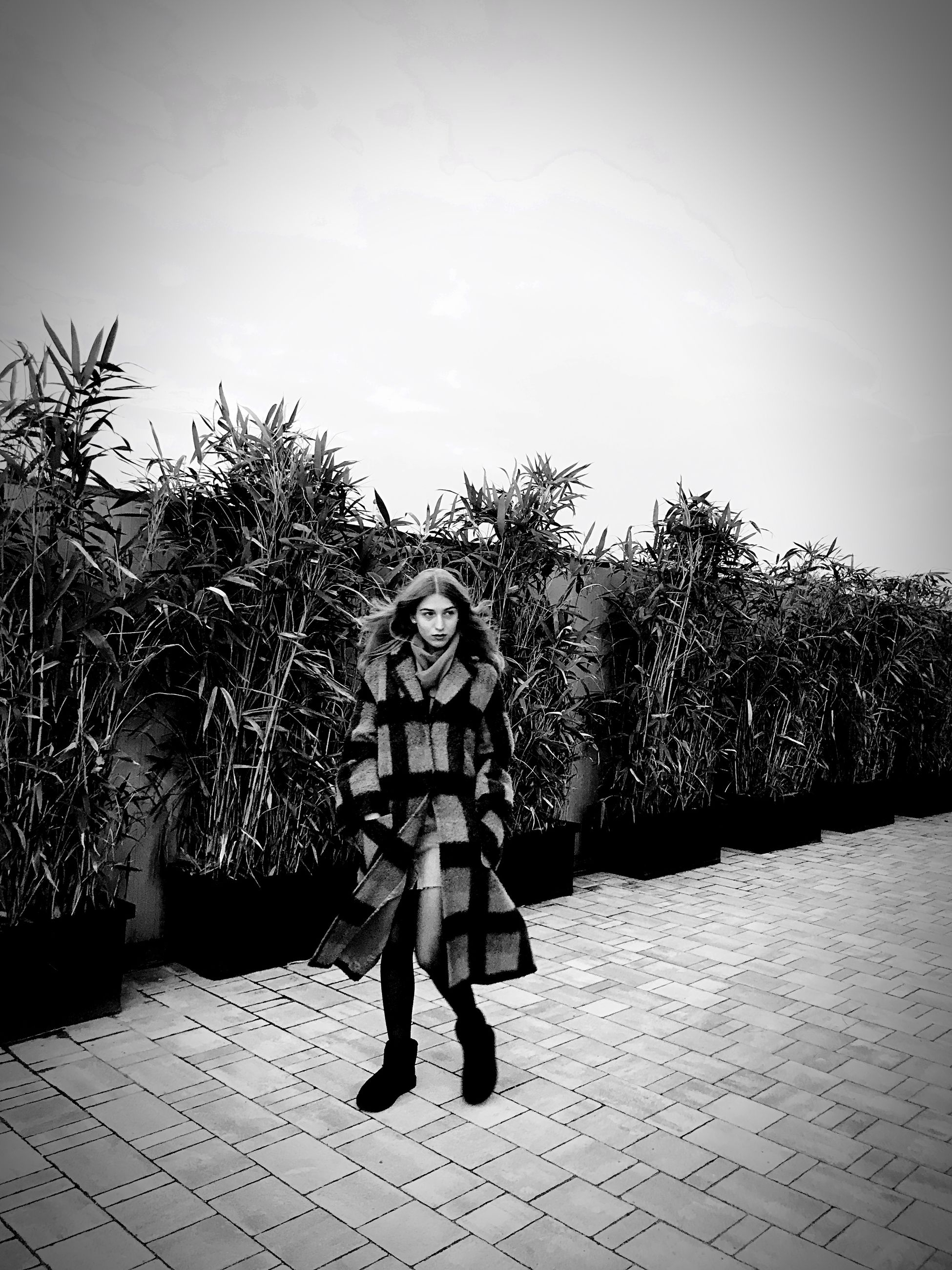 full length, real people, front view, one person, plant, lifestyles, leisure activity, portrait, tree, sky, nature, day, standing, looking at camera, young adult, footpath, outdoors, clothing, warm clothing, paving stone