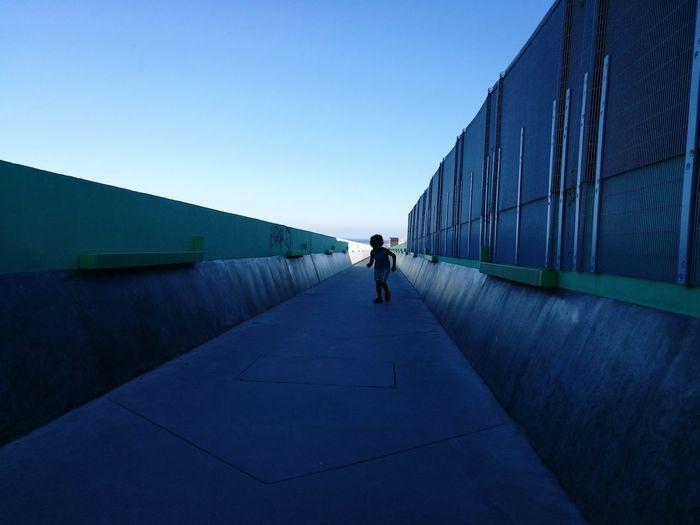 Man walking against clear blue sky