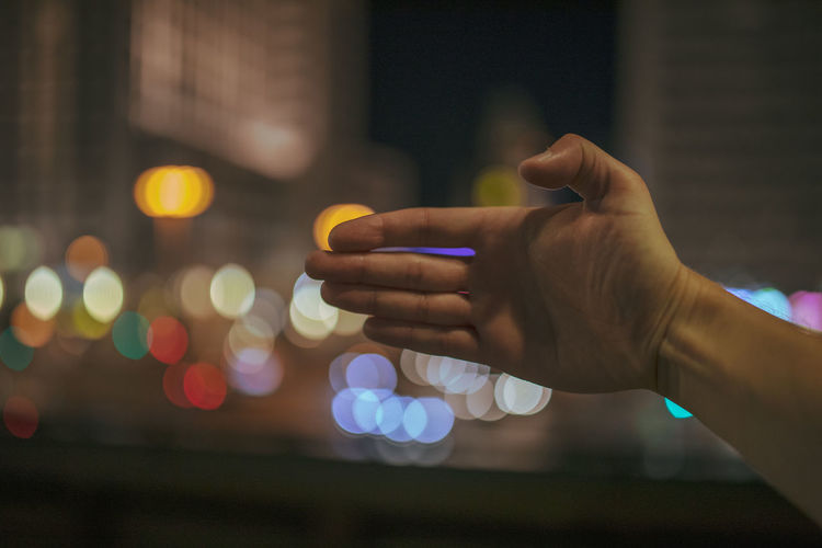 Close-up of hand against illuminated background at night