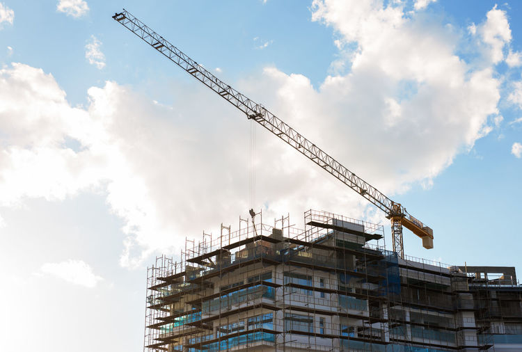 Low angle view of crane in construction site against sky