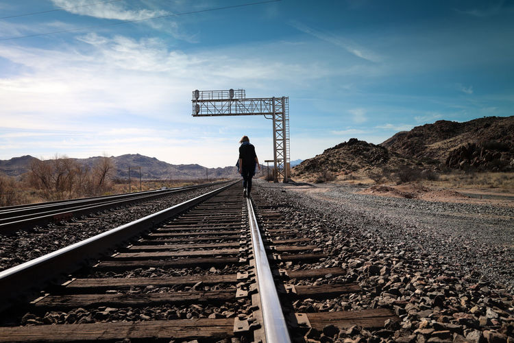 Rear view of woman walking on railroad track against sky