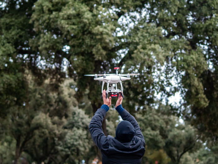 Rear view of man flying drone against trees