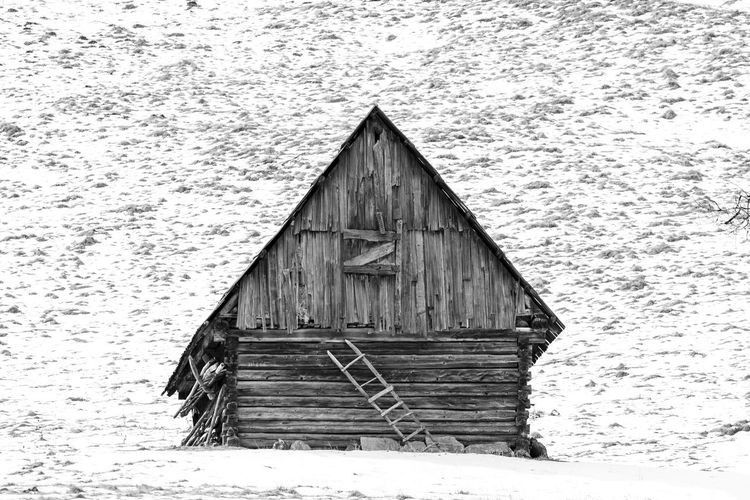 Old wooden house on snow covered field during winter