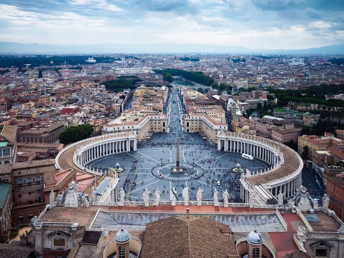 High angle view of st peters square and cityscape against cloudy sky