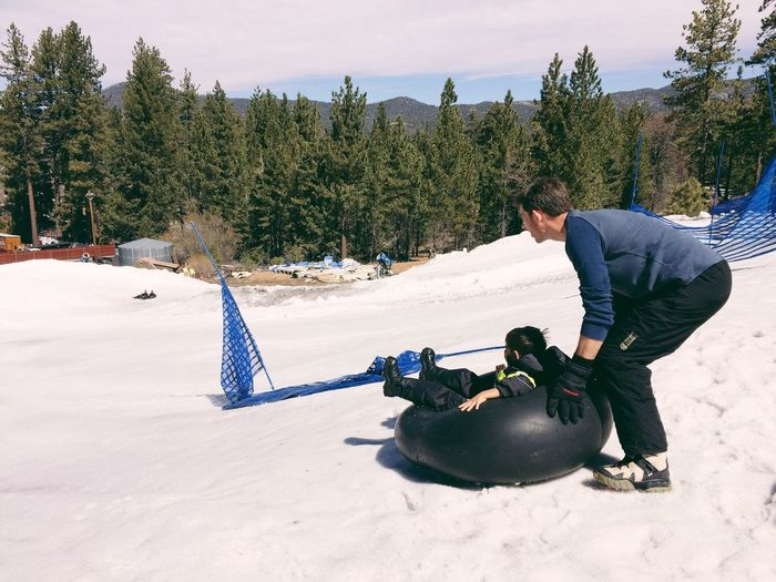 Full Length Of Man Pushing Son Sitting In Inflatable Ring On Snow Covered Hill During Sunny Day
