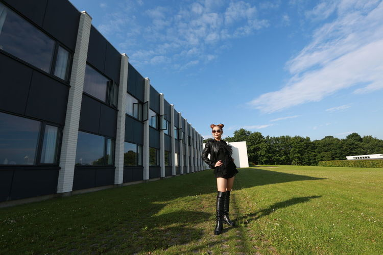 Full length of fashionable woman standing on field by building against sky