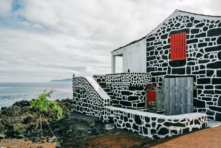 A traditional house made with dark volcanic rocks at a village on Pico Island, Azores, Portugal. Azores Açores Ocean View Pico Island Pico Island Azores Portugal Traditional House Architecture Building Exterior Built Structure Ilha Do Pico Small Village Traditional Architecture Village Volcanic Rock