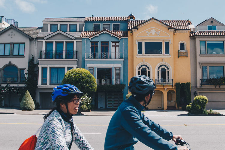 Two people bike by the colorful row houses of San Francisco California. - IG: @LostBoyMemoirs Streetwise Photography Streetphotography Street Photography People People Watching people and places Two People Residential District Street Bicycle San Francisco California The Art Of Street Photography