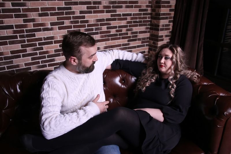 Couple Looking At Each Other While Sitting On Sofa Against Brick Wall